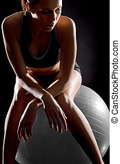 Thoughtful young woman relaxing on fitness ball on black...