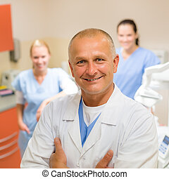 Smiling dental surgeon posing with nurses - Smiling male...