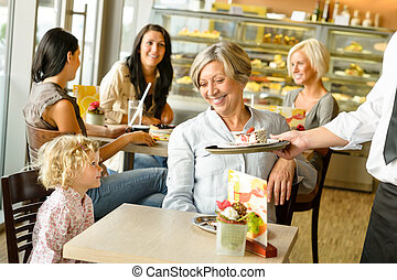Grandmother and grandchild waiting cake order cafe dessert...