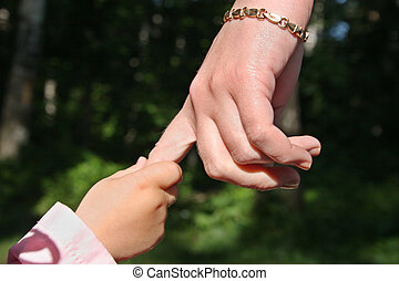 mother\'s  and baby\'s hands in park
