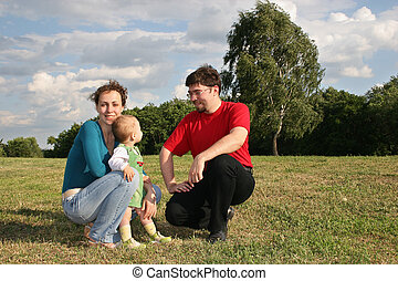 family with baby in the meadow and trees