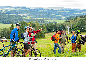 Hikers helping cyclists following track nature landscape -...
