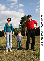 family with son stand on meadow