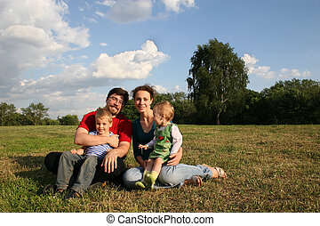 family with two children sit on meadow and trees