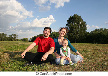 family with baby on meadow and trees 2