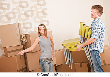 Moving house: Man and woman with box and chair, woman...