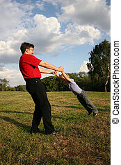 father swings son in the meadow