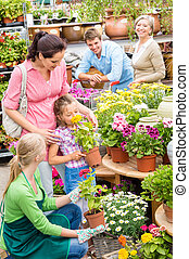 Family garden center shopping for flowers - Little girl with...