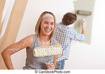 Home improvement: Young couple painting wall with paint...
