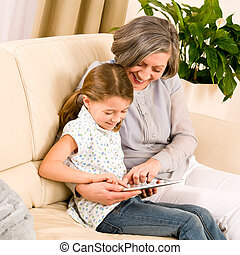 Grandmother with granddaughter use touch tablet -...