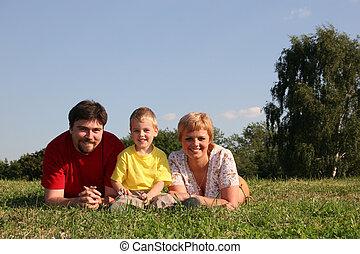 family lies on grass