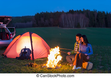 Tent camping car couple sitting by bonfire - Tent camping...
