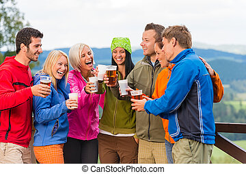 Happy friends clinking glasses drinking beer outdoors -...