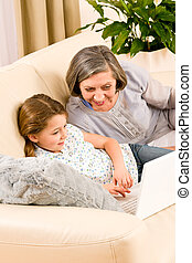 Grandmother with granddaughter use computer - Grandmother...