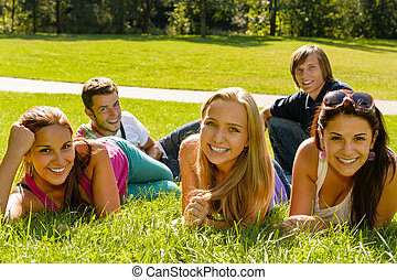 Students laying on grass in park campus smiling relaxing...