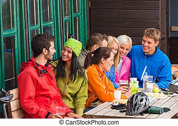 Smiling young friends talking with beer outdoors - Carefree...