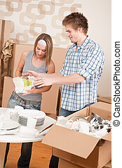 Moving house: Young couple unpacking kitchen dishes, pots,...