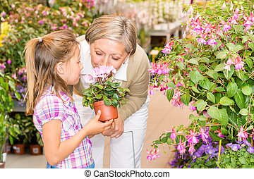 Garden center girl with grandmother smell flower -...