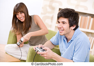 Student - happy teenagers playing video game with control...