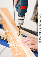 Home improvement - handyman drilling wood in workshop