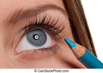 Blue eye, woman applying turqouise make-up pencil - Close-up...
