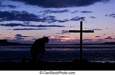 End Of Day Cross - As the day ends a man kneels in pray...