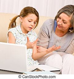 Grandmother and young girl with laptop learn count -...