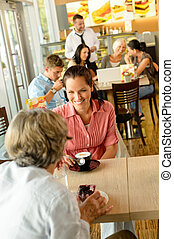 Senior woman with her daughter at cafe drinking eating happy