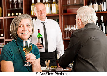 Wine bar senior couple barman discussing - Wine bar senior...