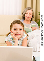 Young girl daydreaming in front of laptop - Young girl using...