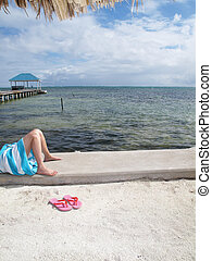 Pink Sandals and Legs - Pink sandals sit in the sand with a...