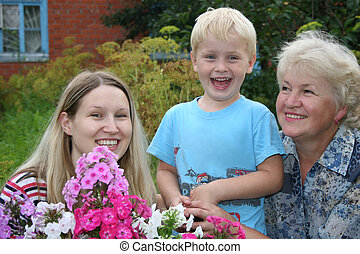 smiling mother with son and grandmother with flowers