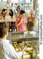 Waiter showing women cakes on window display cafe smiling...