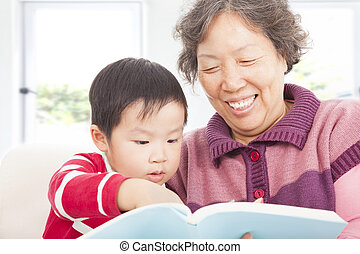 grandmother and grandson are reading story book together