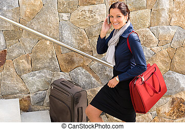 Smiling woman talking phone business traveling rushing
