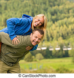 Couple having piggyback ride outside green nature - Young...