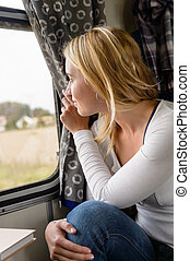 Woman smiling and looking out train window leisure travel...