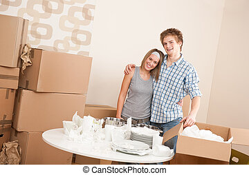 Moving house: Happy man and woman with box and dishes in new...