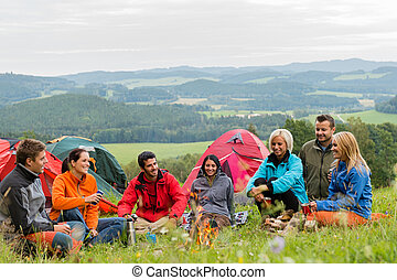 Sitting camping friends with tents and landscape - Smiling...