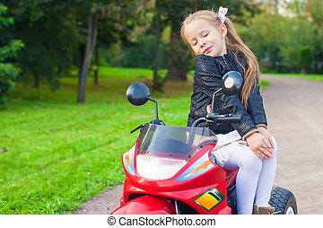 Adorable cute little girl in leather jacket sitting on her...