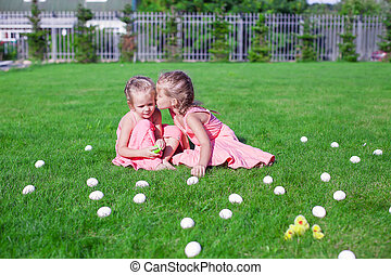 Two adorable little girls having fun with Easter Eggs on...