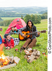 Camping friends lying tents girl playing guitar - Young...