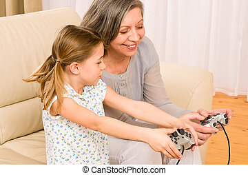 Grandmother and granddaughter play computer game -...
