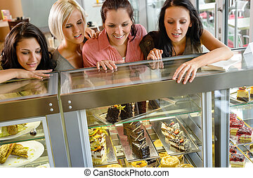 Women friends looking at cakes in cafe craving window...