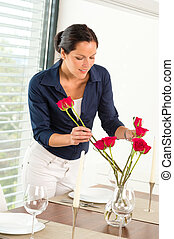 Young woman arranging flowers dinner table preparation