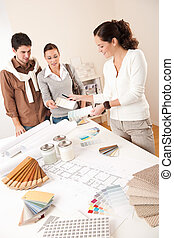 Female interior designer with two clients at office choosing...