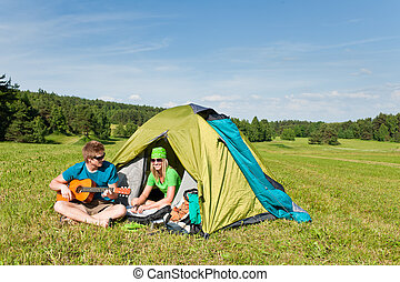 Camping couple play guitar summer in countryside