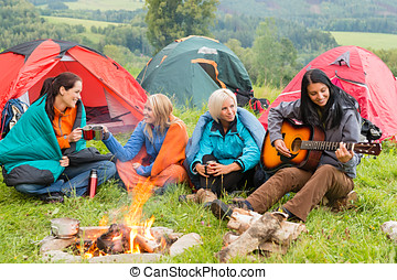 Beside campfire girls sitting listening to guitar - Girls on...