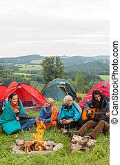 Smiling girls camping on weekend with tents - Young girls...