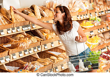 Grocery store: Young woman holding shopping basket